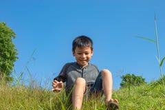 Το ασιατικό αγόρι κάθεται στο βουνό λόφων χλόης στοκ φωτογραφία με δικαίωμα ελεύθερης χρήσης
