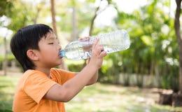 Το ασιατικό αγόρι πίνει το νερό Στοκ Εικόνες