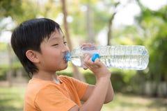 Το ασιατικό αγόρι πίνει το νερό Στοκ Φωτογραφία