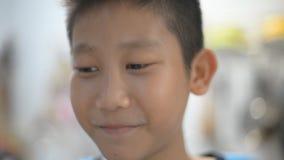 Το ασιατικό αγόρι πίνει το τσάι, το χυμό ή την καυτή σοκολάτα στην κουζίνα φιλμ μικρού μήκους