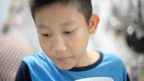 Το ασιατικό αγόρι πίνει το τσάι, το χυμό ή την καυτή σοκολάτα στην κουζίνα απόθεμα βίντεο