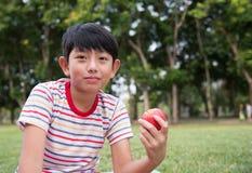 Το ασιατικό αγόρι τρώει το μήλο Στοκ φωτογραφία με δικαίωμα ελεύθερης χρήσης