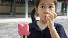 Το ασιατικό γούστο κοριτσιών τρώει την έννοια παγωτού Στοκ Εικόνες
