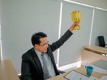 Το ασιατικό επιχειρησιακό άτομο παίρνει το χρυσό τρόπαιο στοκ φωτογραφία με δικαίωμα ελεύθερης χρήσης