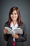 Το ασιατικό επιχειρησιακό κορίτσι διάβασε ότι ένα βιβλίο εξετάζει τη κάμερα Στοκ Εικόνες