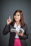 Το ασιατικό επιχειρησιακό κορίτσι κρατά ένα βιβλίο και ένα σημείο επάνω Στοκ εικόνα με δικαίωμα ελεύθερης χρήσης
