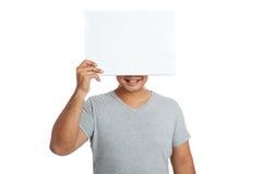 Το ασιατικό ισχυρό άτομο κρατά ότι ένα κενό σημάδι κλείνει το πρόσωπο και το χαμόγελό του Στοκ Φωτογραφία