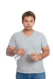 Το ασιατικό ισχυρό άτομο χύνει το νερό σε ένα ποτήρι εξετάζει τη κάμερα Στοκ φωτογραφία με δικαίωμα ελεύθερης χρήσης