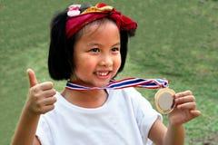 Το ασιατικό κορίτσι αθλητικού πορτρέτου παρουσιάζει χρυσό μετάλλιο Στοκ εικόνες με δικαίωμα ελεύθερης χρήσης
