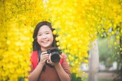 Το ασιατικό κορίτσι παίρνει τη φωτογραφία με το ανθίζοντας κίτρινο λουλούδι Στοκ φωτογραφία με δικαίωμα ελεύθερης χρήσης