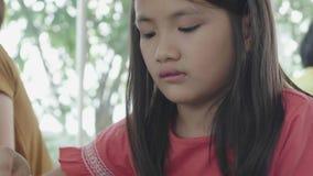 Το ασιατικό κορίτσι παιδιών τρώει το πρόγευμα από το δίκρανο απόθεμα βίντεο