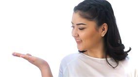 Το ασιατικό κορίτσι παρουσιάζει ένα χέρι στο κενό διάστημα φιλμ μικρού μήκους