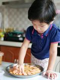 Το ασιατικό κοριτσάκι απολαμβάνει τις φέτες λουκάνικων πέρα από μια ζύμη πιτσών στοκ εικόνες