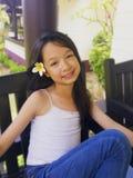 Το ασιατικό μακρύ μαύρο κορίτσι τρίχας φορά το άσπρο λουλούδι πίσω από ri Στοκ Εικόνες