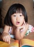Το ασιατικό μικρό κορίτσι διάβασε το βιβλίο της μεγαλοφώνως στοκ φωτογραφία με δικαίωμα ελεύθερης χρήσης