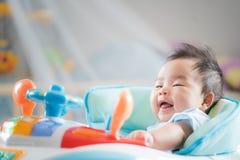 Το ασιατικό μωρό κάθεται ob το παιχνίδι αυτοκινήτων Στοκ Φωτογραφίες