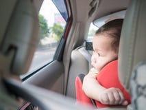 Το ασιατικό μωρό κοιτάζει έξω ενώ καθίστε στο αυτοκίνητο Στοκ Φωτογραφίες