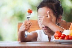 Το ασιατικό παιδί δεν επιθυμεί να φάει τα λαχανικά στοκ εικόνες
