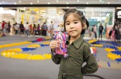 Το ασιατικό παιδί κοριτσιών με την ακολουθία υπηρεσιών παρουσιάζει παιχνίδι αυτοκινήτων Στοκ Εικόνες