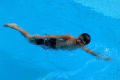 Το ασιατικό παιδί κολυμπά στην πισίνα - το μέτωπο σέρνεται ύφος στοκ φωτογραφίες