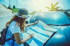 Το ασιατικό ταξίδι γυναικών χαλαρώνει στις διακοπές προσέξτε το χάρτη Εξερευνήστε τη διαδρομή αυτοκινήτων στον τουρισμό στοκ φωτογραφία