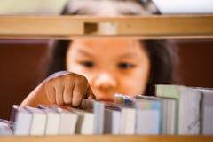 Το ασιατικό χέρι μικρών κοριτσιών βρίσκει και επιλέγει ένα βιβλίο Στοκ φωτογραφία με δικαίωμα ελεύθερης χρήσης