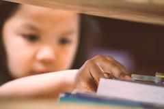 Το ασιατικό χέρι μικρών κοριτσιών βρίσκει και επιλέγει ένα βιβλίο Στοκ φωτογραφίες με δικαίωμα ελεύθερης χρήσης