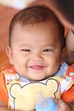 Το ασιατικό χαμόγελο μωρών ευτυχώς και έχει το μπουκάλι του γάλακτος υπό εξέταση Στοκ Φωτογραφία