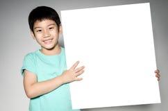 Το ασιατικό χαριτωμένο αγόρι με το μεγάλο άσπρο κενό πιάτο για προσθέτει το κείμενό σας Στοκ φωτογραφίες με δικαίωμα ελεύθερης χρήσης