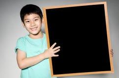 Το ασιατικό χαριτωμένο αγόρι με το μεγάλο μαύρο woodboard για προσθέτει το κείμενό σας Στοκ Εικόνα