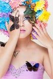 Το ασιατικό όμορφο κορίτσι με ζωηρόχρωμο αποτελεί με τα φρέσκες λουλούδια και την πεταλούδα χρυσάνθεμων Στοκ εικόνα με δικαίωμα ελεύθερης χρήσης