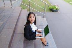 Το ασιατικό όμορφο νέο θηλυκό κρατά στο lap-top και το χαμόγελο χεριών, λ Στοκ Φωτογραφία