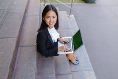 Το ασιατικό όμορφο νέο θηλυκό κρατά στο lap-top και το χαμόγελο χεριών, λ Στοκ φωτογραφία με δικαίωμα ελεύθερης χρήσης