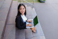 Το ασιατικό όμορφο νέο θηλυκό κρατά στο lap-top και το χαμόγελο χεριών, λ Στοκ Εικόνα