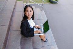Το ασιατικό όμορφο νέο θηλυκό κρατά στο lap-top και το χαμόγελο χεριών, λ Στοκ Εικόνες