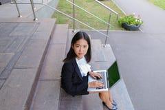 Το ασιατικό όμορφο νέο θηλυκό κρατά στο lap-top και το χαμόγελο χεριών, λ Στοκ εικόνα με δικαίωμα ελεύθερης χρήσης