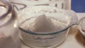 Το ασπράδι και ο λέκιθος μειώνονται στο μεγάλο υαλώδες πιάτο με το αλεύρι σε σε αργή κίνηση απόθεμα βίντεο
