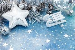 Το αστέρι, το έλκηθρο, οι σφαίρες και το δέντρο έλατου διακλαδίζονται με τους κώνους στο μπλε gli Στοκ φωτογραφίες με δικαίωμα ελεύθερης χρήσης