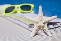 Το αστέρι, η πετσέτα και τα γυαλιά ηλίου θάλασσας επάνω Στοκ Φωτογραφία