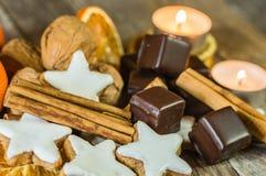 Το αστέρι Χριστουγέννων διαμόρφωσε τα μπισκότα, τη σοκολάτα, τα καρύδια, την κανέλα και τα κεριά στον ξύλινο πίνακα στοκ φωτογραφία