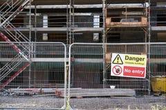 Το ασταθές κτήριο κρατά έξω το επικίνδυνο σημάδι στο φράκτη στην οικοδόμηση του εργοτάξιου οικοδομής στοκ φωτογραφίες με δικαίωμα ελεύθερης χρήσης
