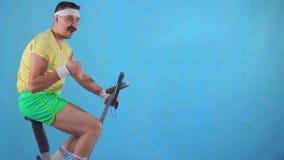 Το αστείο άτομο από τη δεκαετία του '80 με ένα mustache στο ποδήλατο άσκησης σε ένα μπλε υπόβαθρο, παρουσιάζει αντίχειρα επάνω αρ απόθεμα βίντεο