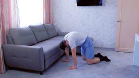Το αστείο άτομο nerd κάνει την τεντώνοντας άσκηση για την πίσω στάση σε όλα τα fours στο σπίτι Έννοια αθλητικού χιούμορ απόθεμα βίντεο