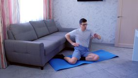 Το αστείο άτομο nerd κάνει τη διαμόρφωση των ασκήσεων χεριών καθμένος στο χαλί στο σπίτι Έννοια αθλητικού χιούμορ απόθεμα βίντεο