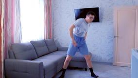 Το αστείο άτομο nerd κάνει τις ασκήσεις αερόμπικ zumba στο σπίτι Έννοια αθλητικού χιούμορ απόθεμα βίντεο