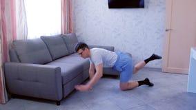Το αστείο άτομο nerd κάνει τις τεντώνοντας ασκήσεις ικανότητας που στέκονται σε όλα τα fours στο σπίτι Έννοια αθλητικού χιούμορ απόθεμα βίντεο