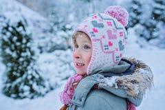 Το αστείο έκπληκτο κορίτσι παιδιών μέσα με το μειωμένο χιόνι Στοκ φωτογραφία με δικαίωμα ελεύθερης χρήσης