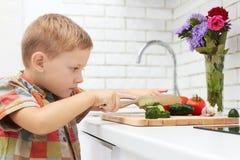 Το αστείο αγόρι παιδιών θέτει τον πίνακα για το γεύμα λίγος αρχιμάγειρας κόβει τα λαχανικά Στοκ Εικόνες