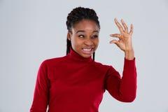 Το αστείο αφροαμερικανός πρόσωπο μορφασμών κοριτσιών και παρουσιάζει αντίχειρες επάνω μικρό μέγεθος Στοκ Φωτογραφία