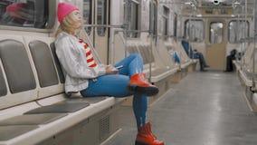 Το αστείο ελκυστικό χαρούμενο ξανθό κορίτσι που χορεύει σε ένα αυτοκίνητο υπογείων στο υπόγειο μετρό Η γυναίκα είναι ακούει τη μο απόθεμα βίντεο